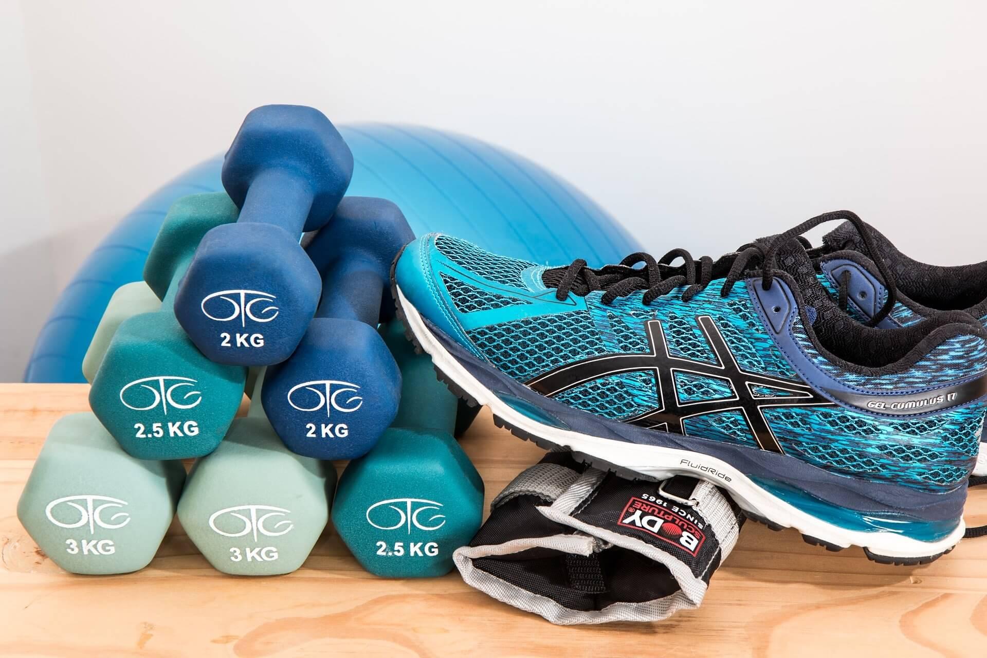 Conjunto de pesas y una zapatilla de deporte sobre una mesa